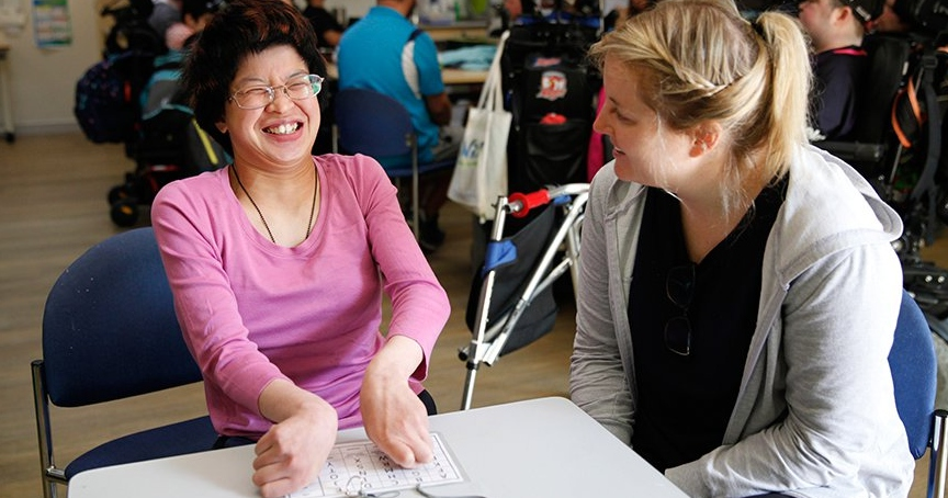 Two women sitting at a table laughing and talking