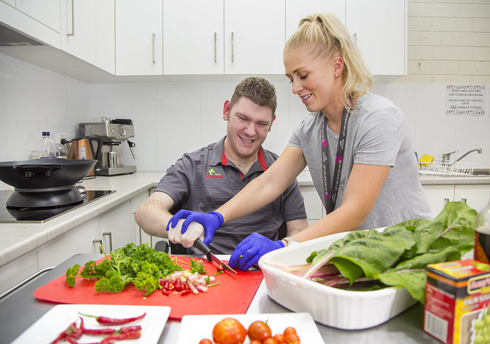 Man being supported to cut vegetables in a kitchen