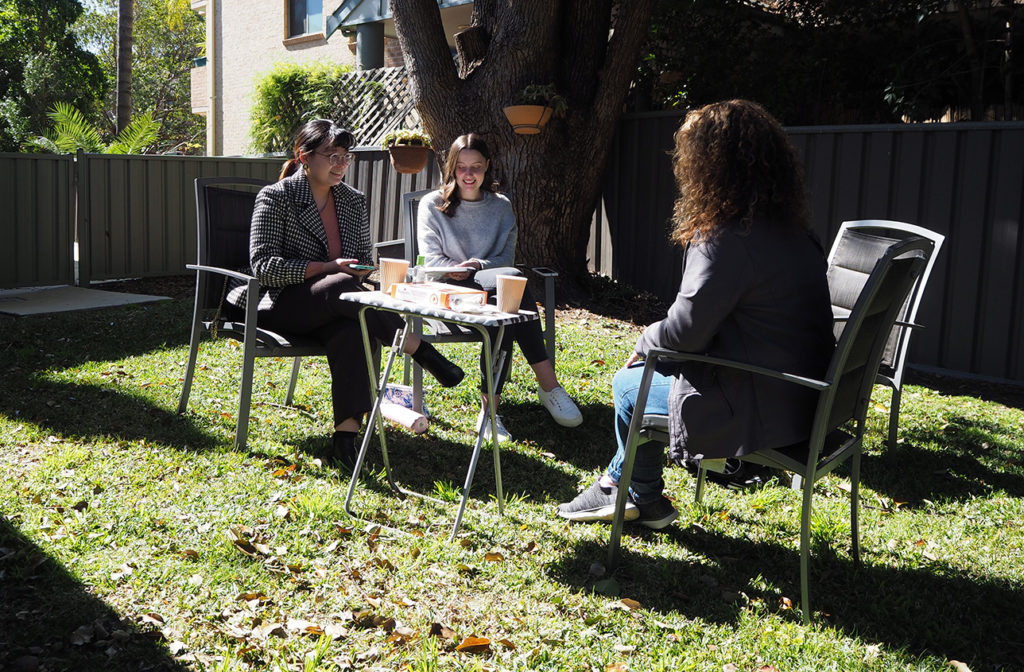 UTS students talking to a Northcott staff member, sitting outside